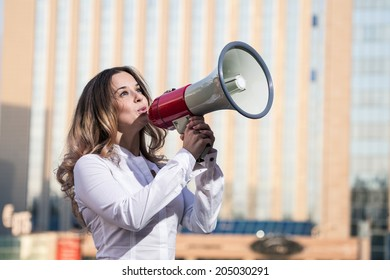 Stylish businesswoman holding a megaphone outdoors