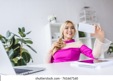 stylish businesswoman taking selfie on smartphone at workspace with laptop