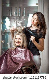 Stylish by professionals you can trust. Mirror reflection of a young beautiful hairdresser doing her clients hair with a hair drier on the background of the hairdressing salon