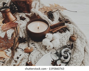 Stylish candle with jewelry and autumn leaves, cotton,nits, acorns on white sweater. Cozy fall image.