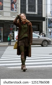 Stylish carefree girl crosses the road at the crosswalk. She is dressed in the style of boho: brown coat, yellow bag, green sweater, shorts and torn stockings