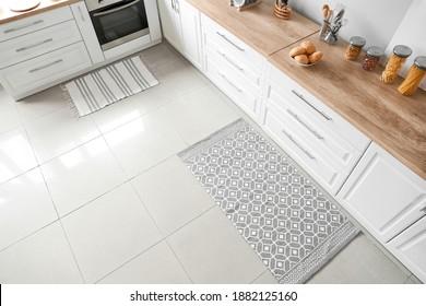 Stylish carpet on floor in modern kitchen - Shutterstock ID 1882125160
