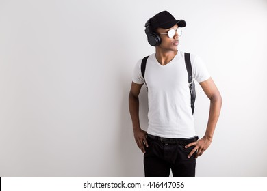 Stylish casual african american guy with sunglasses, cap and headphones on light background with copy space