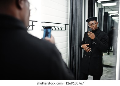 Stylish casual african american man at black beret and overcoat at fitting room clothes store, making photo at mirror on his phone camera.