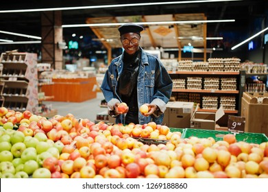 Stylish casual african american man at jeans jacket and black beret checking apple fruits in organic section of supermarket.