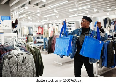 Stylish casual african american man at jeans jacket and black beret with fanny pack or waist bag holding blue shopping bags at clothes store.
