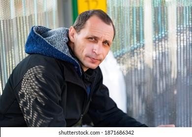 Stylish casual caucasian man wear blue hooded jacket and black jacket posing against grey wall. Handsome male model wear jacket