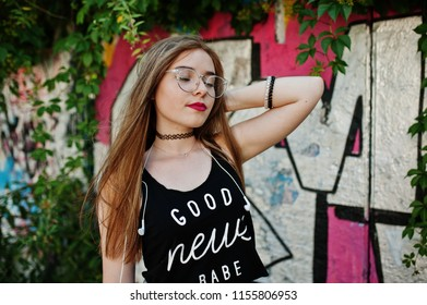 Stylish casual hipster girl in cap, glasses and jeans wear, listening music from headphones of mobile phone against large graffiti wall.