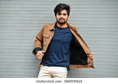 Stylish casual indian man wear blue t-shirt and brown jacket posing against grey wall.
