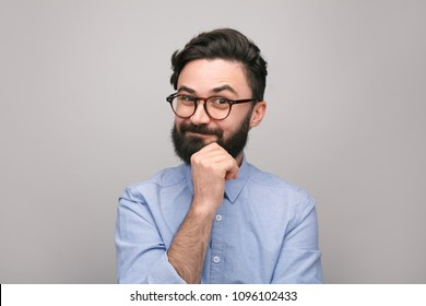 Stylish casual man with beard wearing eyeglasses and looking skeptically at camera on gray background.