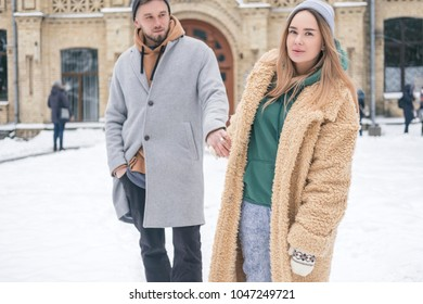 Stylish caucasian couple of man and woman waling in the european city park in winter. Cold, snowy day. Space for text
