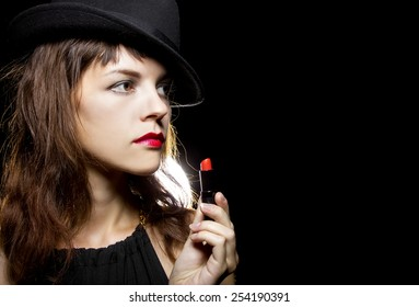 stylish caucasian female putting on red lipstick on black background