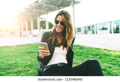 Stylish caucasian female wearing sunglasses chatting online on a mobile phone while sitting in a park on a sunny day. Student girl having video call with friend outdoors during leisure time.