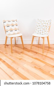 Stylish chairs with ornamental cushions, on hardwood floor. Contemporary home decor.