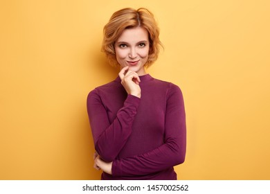 stylish cheerful cunning woman thinking with finger on chin. Happy pensive woman planning her weekend. positive emotion . close up portrait. isolated yellow background