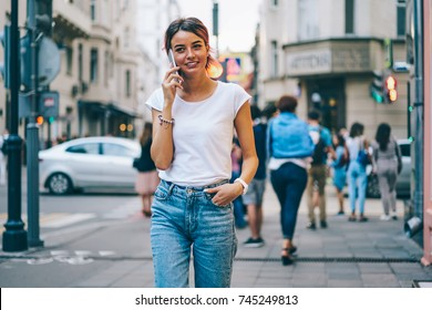 Stylish cheerful young woman dressed in white t-shirt with mock up area for text message strolling in street of modern city and talking with friend on telephone.Colorful promotional background