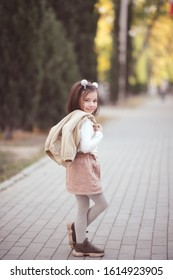 Stylish child girl 3-4 year old holding jacket walking on street outdoors. Looking at camera. Childhood.
