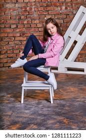 e60e524f39e7e Stylish child girl sitting fashion pose on chair. Beautiful glamorous kid  teenager. Casual,