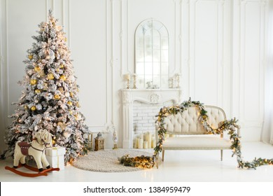 Stylish Christmas light interior with a soft armchair or sofa decorated with garland. Comfort home. Christmas tree with presents underneath in living room