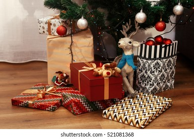 stylish christmas presents in modern wrapping paper. luxury golden gifts and toys under beautiful christmas tree in room. seasonal greetings concept