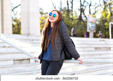 Stylish city portrait of ginger petty woman, walking alone at Europe city center, wearing winter jacket sweater, trendy modern mirrored sunglasses, cheerful mood, travel with backpack, sunny cold day.