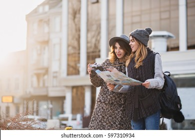 Stylish city portrait of two fashionable girls walking in Europe modern city centre. Fashionable friends traveling with backpack, map, camera, making photo, tourist, get a lost, place for text