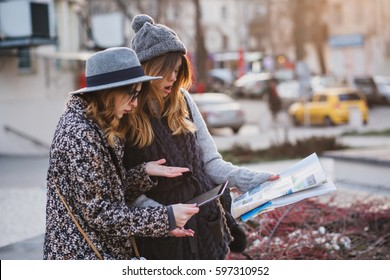 Stylish city portrait of two fashionable girls trying to find the location on the map in Europe city centre .Fashionable friends traveling with backpack, map, camera, tourist, get a lost