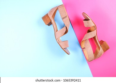 Stylish classic beige women's leather sandals shoes with medium heels shot from the side on pink blue multi-colored paper background. Copy space, top view, flat lay. Shoe sale / clearance ad concept.