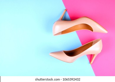 Stylish classic women's beige leather shoes with medium high heels, side shot on pink blue multi-colored paper background. Copy space, top view, flat lay. Shoe sale / clearance ad concept.