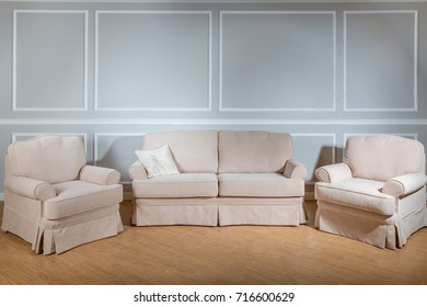Stylish classical style sofa and two chairs in a beige tint on the background of a gray wall and a wooden floor