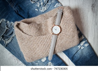 Stylish clock on a sweater and torn jeans. Fashionable concept