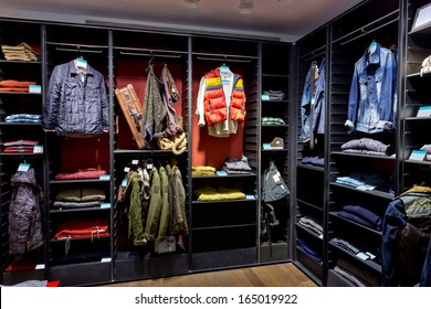 Stylish clothes on hangers in shop