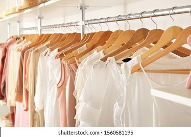 Stylish clothes on hangers in show room
