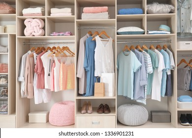 Stylish clothes, shoes and accessories in large wardrobe closet