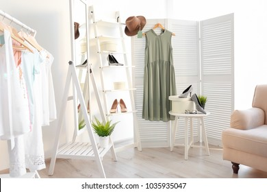 Stylish clothes and shoes in dressing room. Fashionable wardrobe