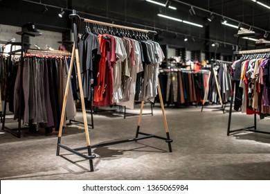 Stylish clothing store with dark ceiling with hanging luminous lamps and brick walls. There are many stands with hangers with different colorful clothes, shelves with shoes. Horizontal.
