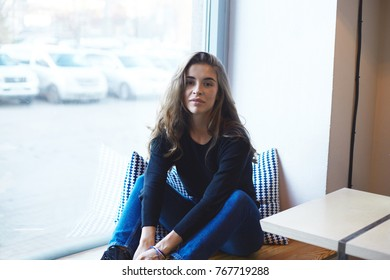 Stylish college student in black top and jeans sitting on windowsill at coffee house, waiting for her drink at daytime with urban landscape outside. Modern lifestyle, people and leisure concept