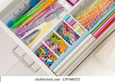 Stylish colored stationery in pastel colors. Female workplace. Organization of a drawer at the workplace. Storage and order of office supplies. Concept back to school.