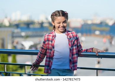 Stylish and comfortable to wear. Happy stylish child outdoor. Little cute girl with brunette hair wearing stylish plaid shirt on sunny day. Small fashion model smiling with stylish casual look.