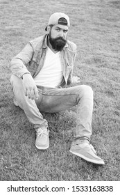 Stylish and comfortable to wear. Stylish hipster in baseball cap sitting on green grass outdoor. Bearded man wearing stylish summer streetwear. Fashion model with stylish casual look.
