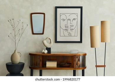 Stylish composition of creative living room interior with mock up poster frame, wooden commode, lamp, mirror, dry banch in vase and elegant personal accessories. Neutral beige wall. Template.