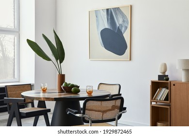 Stylish composition of dining room interior with design table, modern chairs, decoration, tropical leaf in vase, fruits, bookcase, abstract mock up paintings and elegant accessories in home decor.