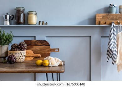 Stylish composition of kitchen interior with wooden family table, vegetables, tea pot, dessert , plants and kitchen accessories in gray concept of home decor.
