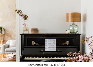 Stylish composition at living room interior with black piano, dried flowers in vase, gold clock, design lamp, boxes, copy space and elegant presonal accessories in modern home decor.