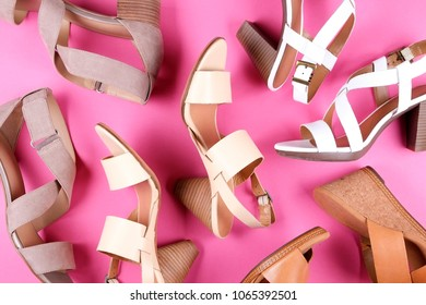 Stylish composition with multiple classic women's leather sandals shoes with medium heels, different styles, on pale pink background. Copy space, top view, flat lay. Shoe sale / clearance ad concept.
