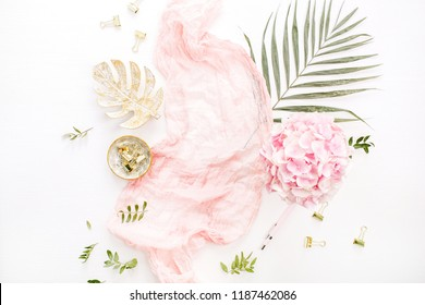 Stylish composition with pink hydrangea flowers bouquet, tropical palm leaf, pastel blanket, monstera leaf plate and accessories on white background. Flat lay, top view rose gold desk.