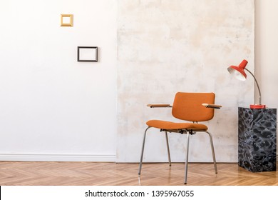 Stylish compositon of retro home interior with mock up phot frames, vintage orange chair, marble stand, design lampsand abstract paintings. Minimalistic concept. Nice home decor.