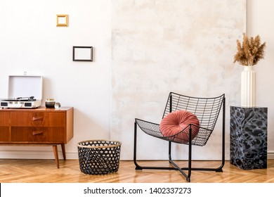 Stylish compositon of retro home interior with mock up phot frames, vintage cupboard,white  gramophone, marble stand, design armchair and abstract paintings. Minimalistic concept. Nice home decor.