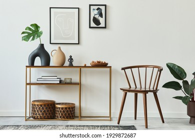 Stylish concept of living room interior with mock up poster frames, wooden console, chair, tropical leaf in vase, rattan baskets, plant, carpet and personal accessories in home decor. Template.