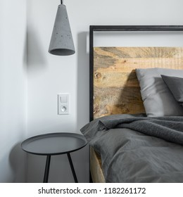 Stylish concrete lamp, industrial wooden bed and metal side table in bedroom